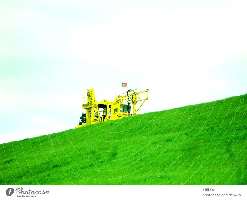 Schieflage Bagger gelb grün Wolken Rasen Himmel diagonal Textfreiraum oben Textfreiraum unten Hügel Damm