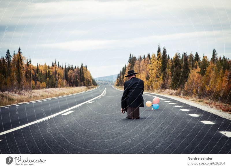 Trauriger Mann sitzt auf einem Koffer an einer einsamen Landstraße Ferien & Urlaub & Reisen Mensch maskulin Erwachsene Landschaft Herbst Wald Straßenverkehr