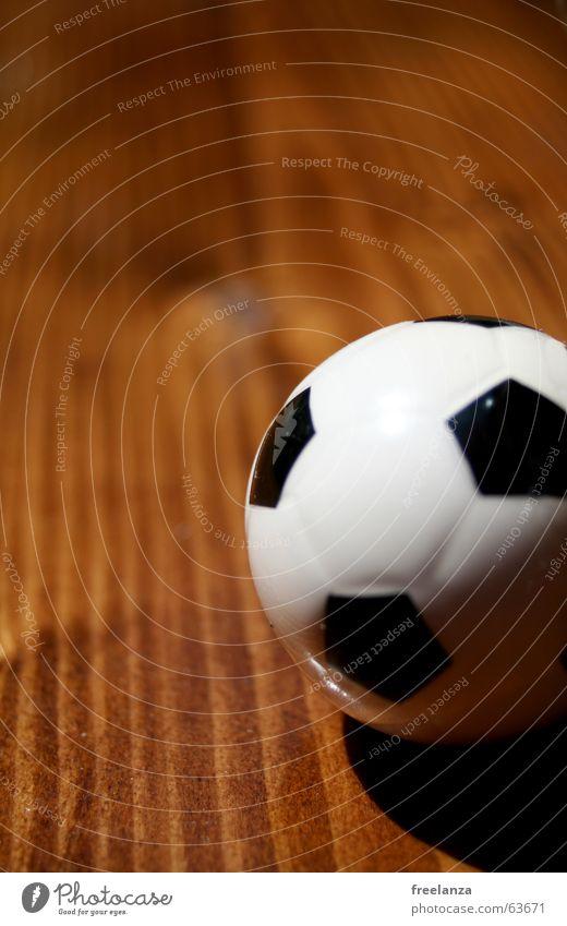 Der Ball ist rund und .......... weiß schwarz Schwache Tiefenschärfe Farbfoto 1 Fußball Miniatur Holzuntergrund Maserung Textfreiraum oben winzig Menschenleer