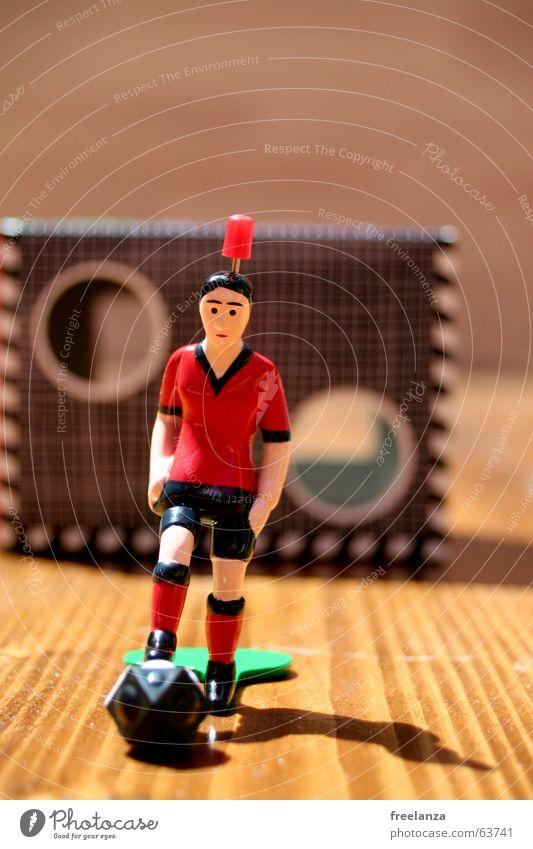Der Ball hat Ecken 2.... rot schwarz grün braun Holz weiß Schatten Statue Sport torwand Tischfußball Maserung 1 Schwache Tiefenschärfe Farbfoto Tor Loch