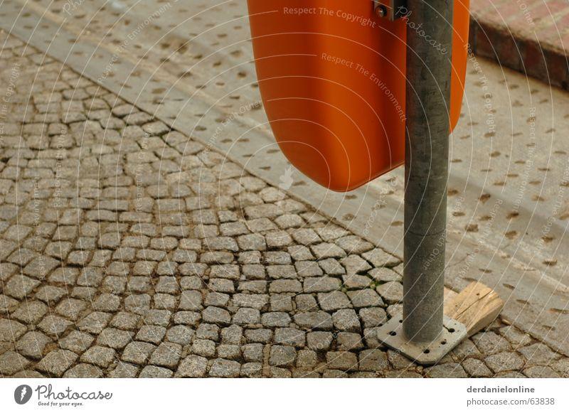 Stadtmöbel grau Müllbehälter Papierkorb Kopfsteinpflaster alt dreckig orange holzkeil Pfosten
