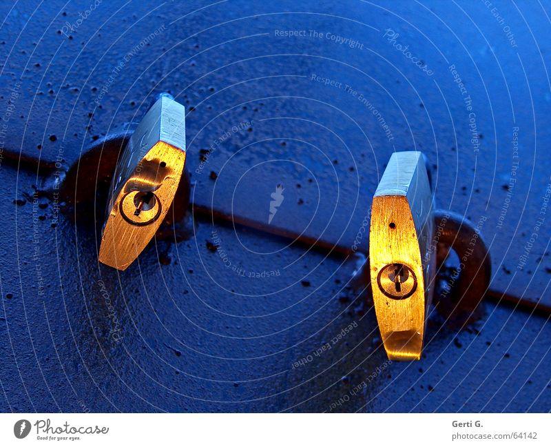 zwei goldene Vorhängeschlösser mit Schlüsselloch an blauer Oberfläche Sicherheit schließen geschlossen Vorhängeschloss 2 Zusammensein Licht Stimmung Dämmerung