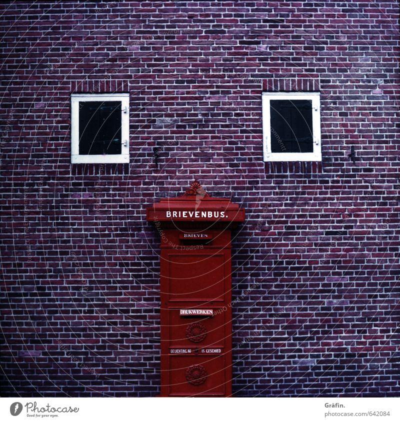 I see faces Bauwerk Gebäude Fassade Fenster Briefkasten Stein retro Stadt rot Genauigkeit planen Surrealismus Symmetrie Backsteinfassade Wand Farbfoto