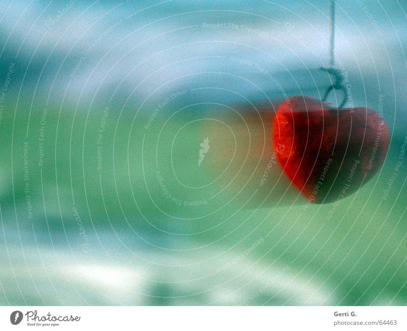 rotes Herz mit Bewegungsunschärfe am rechten Bildrand vor grün-blauem Hintergrund Geschwindigkeit Schwung Swing Schnur Liebe Frieden anhängsel herzrasen Dynamik