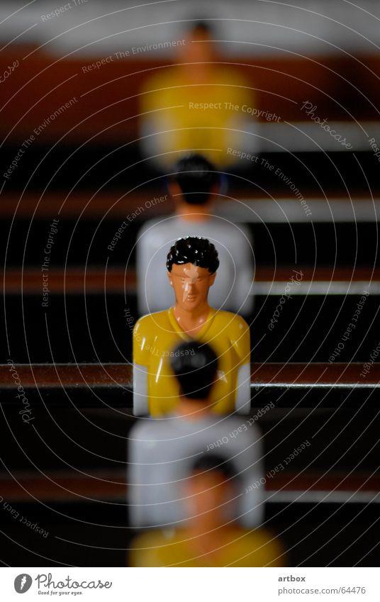 Mann gegen Mann Tischfußball bewegungslos Unschärfe Spielen Gegner Trikot gelb weiß Spielfigur Stab unbewegt Linie Reihe Schwache Tiefenschärfe hintereinander