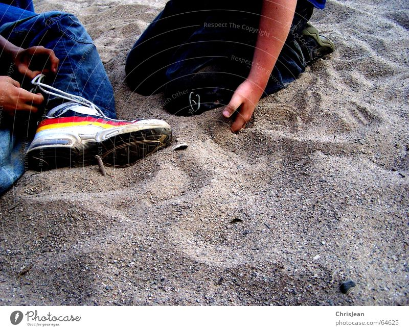 Titellos Mensch Hand Sand 2 Schuhe sitzen Jeanshose Hose Knoten binden Schuhbänder Sandkorn Schuhsohle Fußballschuhe
