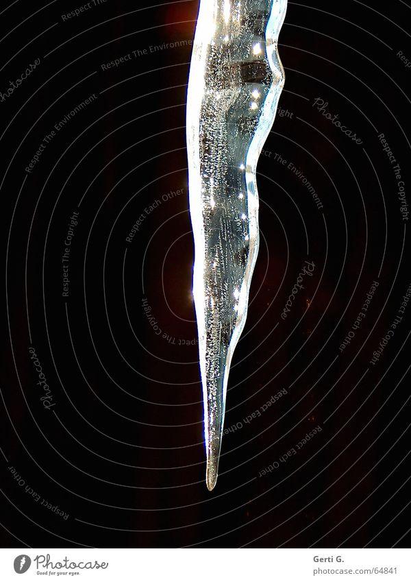 die Spitze eines Eiszapfen ragt vor schwarzem Hintergrund ins Bild weiß gefroren hängen frieren Eiszeit dunkel Winter Schwäche black glänzend Frost dark hell