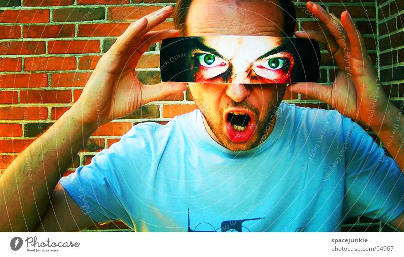 Die Welt mit anderen Augen sehen Mann böse Wut Porträt Freak Angst beängstigend dunkel schwarz verrückt grün Mauer Backstein Gesicht Blick Mensch T-Shirt blau