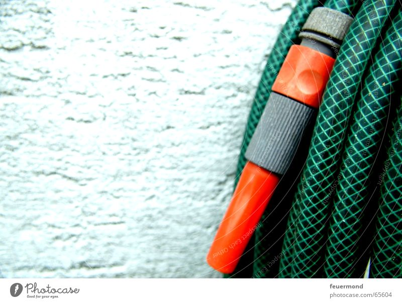 Gartenschlauch statt Gießkanne Wasser grün Wand Regen orange Putz spritzen gießen Schlauch Kühlung Wasserschlauch