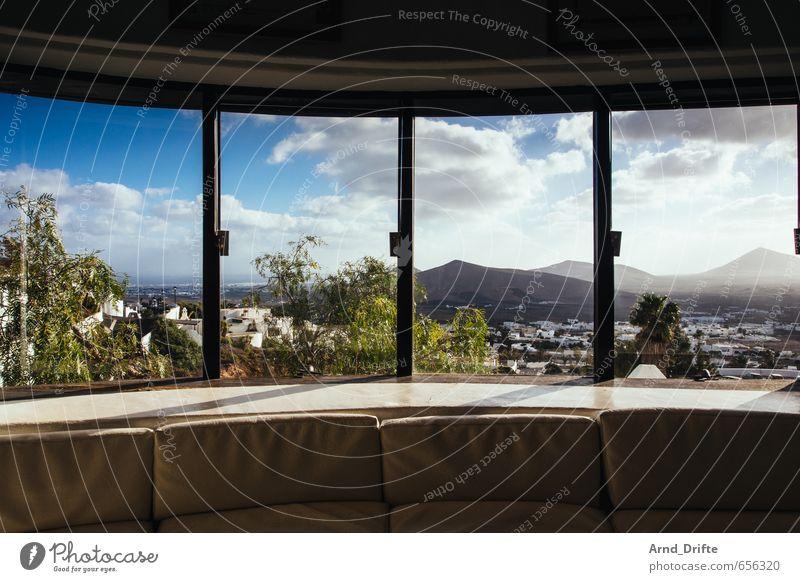Fensterfront Häusliches Leben Wohnung Traumhaus Innenarchitektur Möbel Sofa Raum Landschaft Himmel Wolken Berge u. Gebirge blau Geborgenheit Warmherzigkeit