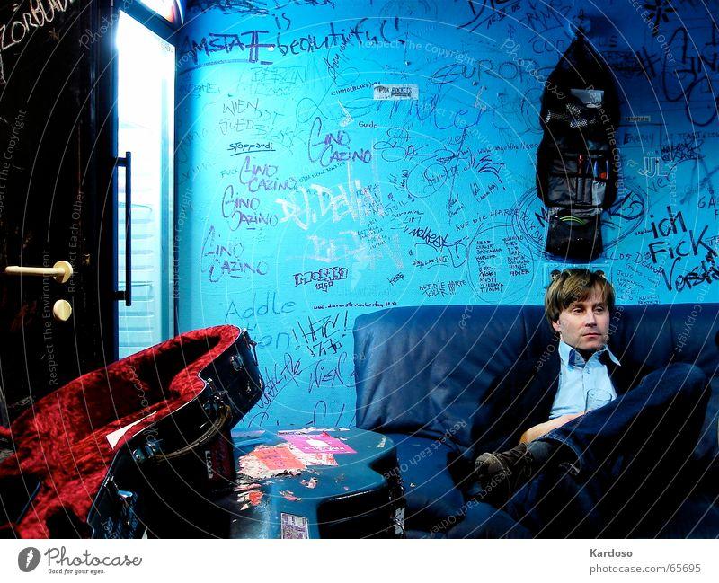 Backstage Blues Mann blau Graffiti warten Koffer Sofa Neonlicht Wien Künstler Kühlschrank Gitarrenkoffer