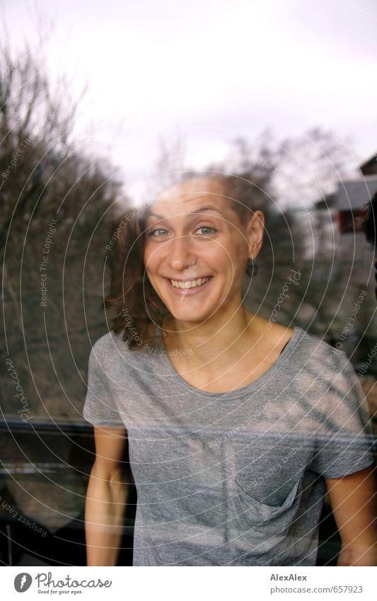 Portrait einer lachenden jungen Frau hinter einer Fensterscheibe Junge Frau Jugendliche Haare & Frisuren Gesicht 18-30 Jahre Erwachsene T-Shirt brünett