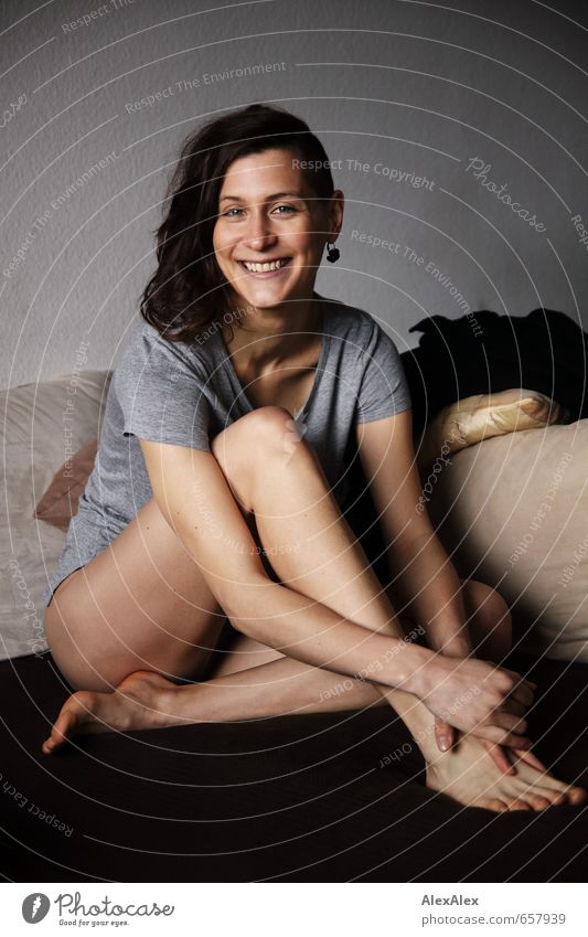 junge, sportliche Frau mit langen Beinen sitzt barfuß auf der Couch und lächelt Wohnzimmer Sofa Kissen Junge Frau Jugendliche Gesicht Barfuß 18-30 Jahre