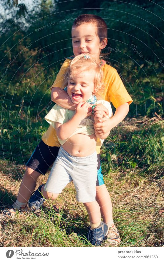 Mensch Kind grün Sommer Mädchen Freude Gefühle Junge Gras Spielen Garten Familie & Verwandtschaft blond Kindheit Lächeln T-Shirt