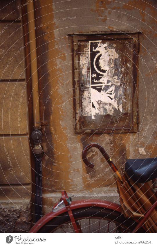 Gemälde Wand Mauer Gemäuer Putz Plakat plakatieren Fahrrad Regenschirm malerisch Verfall Stillleben vergessen Ocker beige kaputt Papier Sockel Vergangenheit