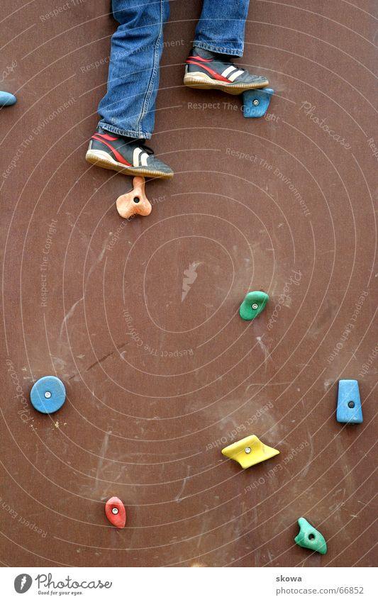 bergsteigen auf'm Spielplatz Kletterwand mehrfarbig Schuhe Geschicklichkeit braun Hose Wand Klettern Beine hoch Jeanshose