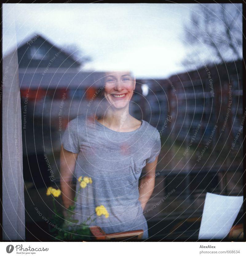 Ausblick auf Balkonistan Junge Frau Jugendliche Kopf Grübchen 18-30 Jahre Erwachsene Blume Mehrfamilienhaus Fensterscheibe T-Shirt brünett langhaarig Lächeln