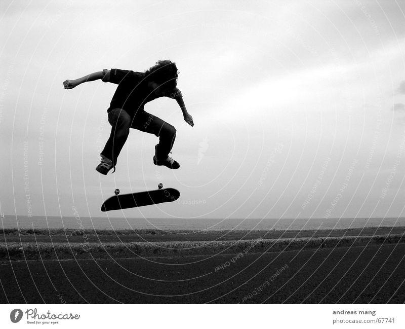 Kickflip am Meer Skateboarding Salto springen Bordsteinkante Stil Trick Aktion Sport extrem fliegen geschmackvoll Parkdeck Junge boy Straße road ocean sea Rolle