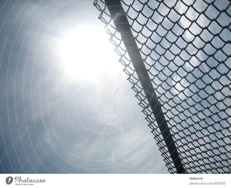 Den Blick durch einen Maschendrahtzaun auf die Sonne und den blauen Himmel richten. Zaun Borte weiß Niveau hoch Trennung
