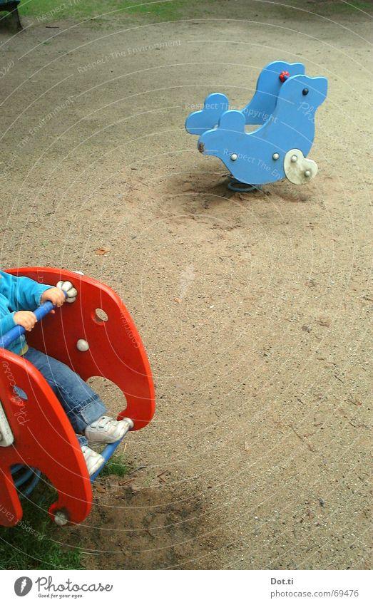 riding through the prairie Kind blau rot Freude Einsamkeit Spielen Bewegung Sand Park leer Bodenbelag Flügel festhalten Spielzeug Kleinkind Fußspur