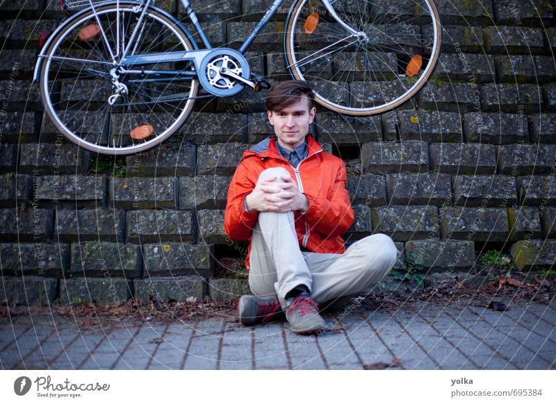 Junger Mann mit Fahrrad, der draußen auf dem Boden posiert. Mensch maskulin Jugendliche 1 18-30 Jahre Erwachsene Jugendkultur Umwelt Frühling Herbst Stadt Mauer