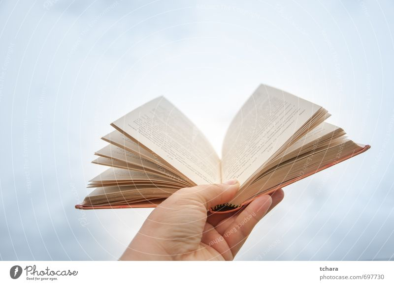 Buch öffnen Tisch Bildung Schule Frau Erwachsene Hand Himmel Wolken Papier hell neu blau orange weiß offen Handbuch Page Fotografie Farbbild Einzelobjekt