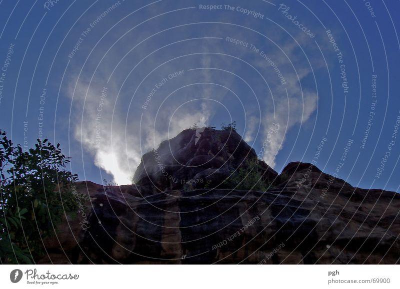 Rauchender Kopf Himmel blau schwarz Nebel Felsen Wasserdampf