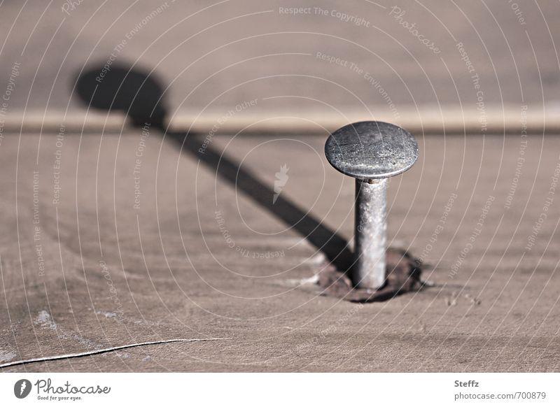 ein Nagel wie eine Sonnenuhr Nagelkopf Metall Holz reparieren einfach Schattenspiel Zeitmessung Schattenseite nageln beige Holzbrett Handwerk einzeln