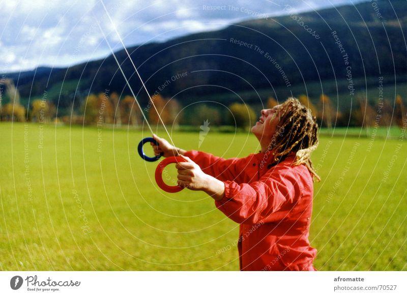 Roter Rastadrachensteiger Jugendliche rot Junger Mann 18-30 Jahre Erwachsene Herbst Bewegung Wiese Gras Freizeit & Hobby Wind Kreis Schnur Konzentration Jacke