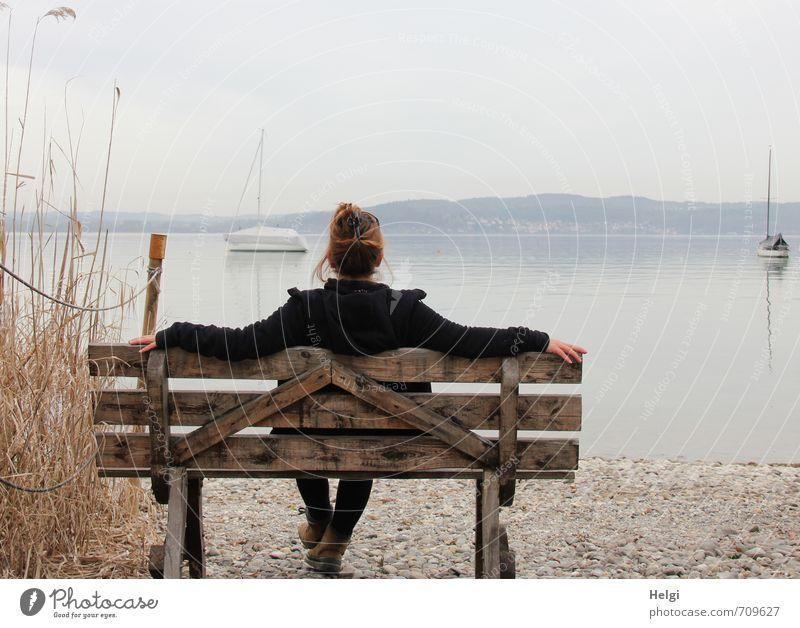 Rückansicht einer Frau mit hochgesteckten brünetten Haren und dunkler Jacke sitzt auf einer Holzbank und schaut auf einen See im Nebel Wohlgefühl Erholung ruhig