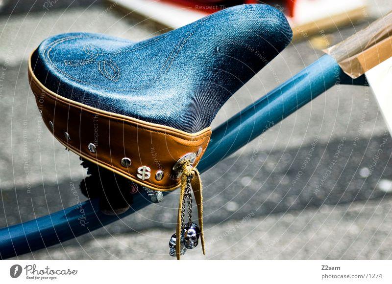 jeans seat blau braun Fahrrad sitzen Jeanshose Sitzgelegenheit Stab Schädel Gefolgsleute Fahrradsattel