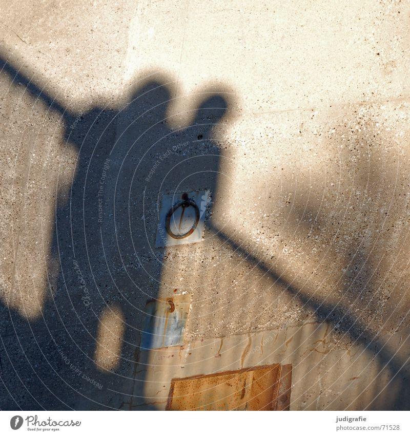 Schatten 2 Zusammensein Wand Mauer Beton Licht Mensch Paar Geländer Linie Kreis Metall Rost Sonne paarweise