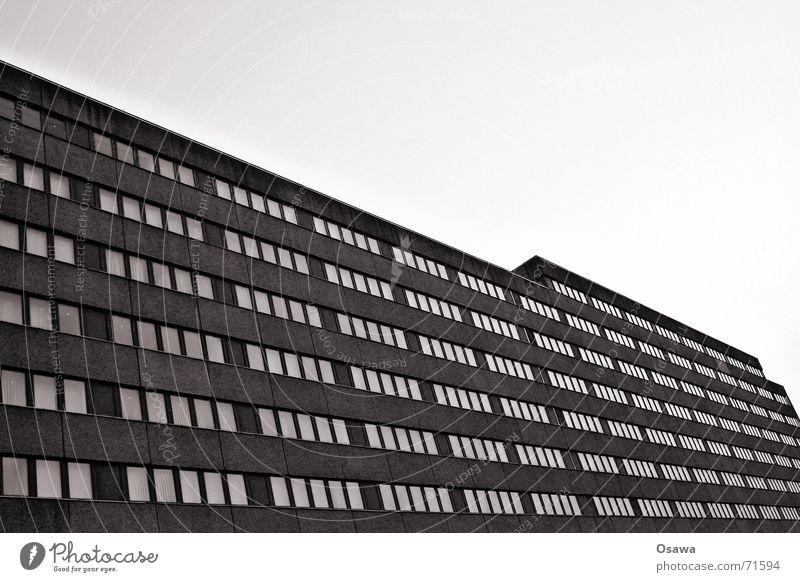 Plattenbau Bürogebäude Lichtenberg Haus Gebäude Fassade Beton Fenster Raster Osten Berlin Himmel DDR trist Architektur Schwarzweißfoto dunkel Froschperspektive