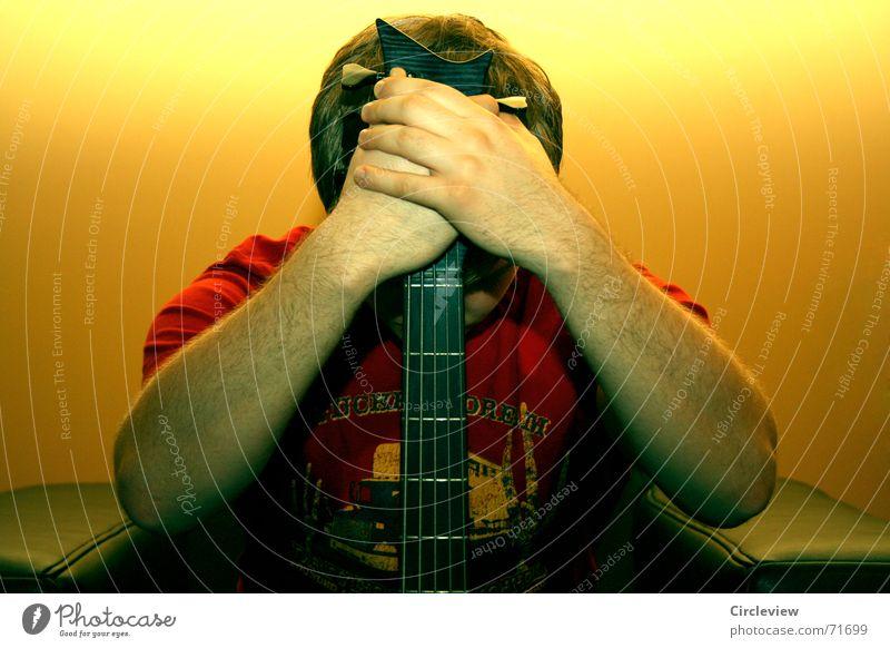Stille - kein Ton Denken Mann Trauer ruhig Hand T-Shirt rot Wand gelb dunkel Musikinstrument Sessel Griff Halt Gedanke Pause Blitzlichtaufnahme edel Gefühle
