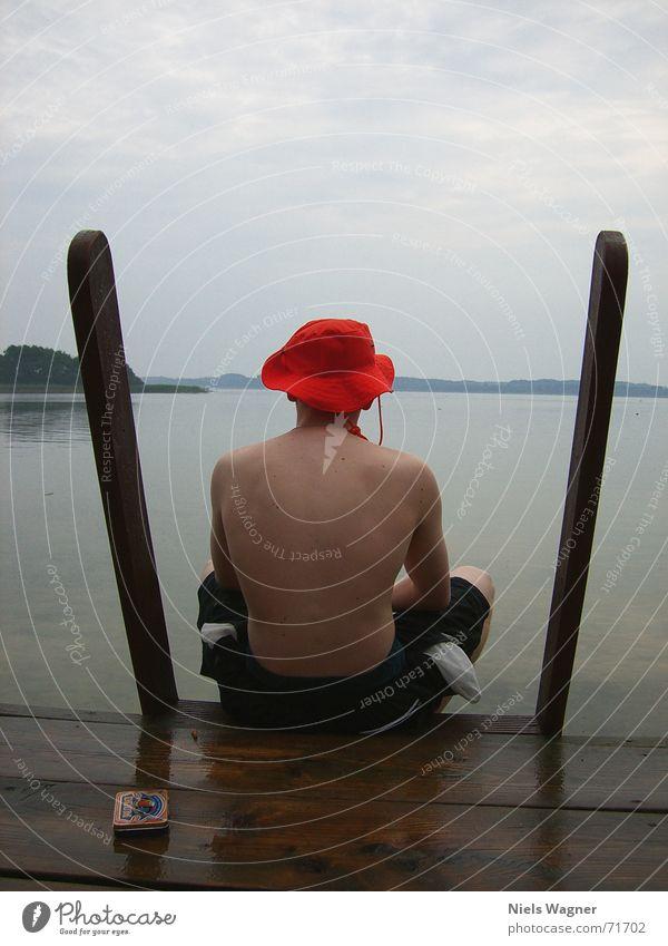 Einsamer Bube See nass Reflexion & Spiegelung Holz Badehose flo Wasser Regen Körper Rücken Hut orange Schwimmen & Baden