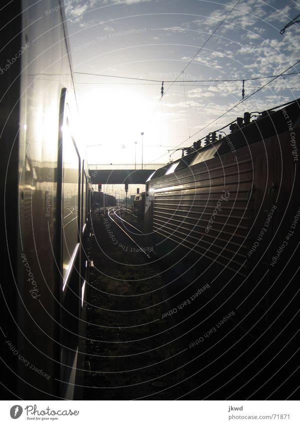 Zwischen den Gleisen Eisenbahnwaggon glänzend Lokomotive schwarz Sonnenaufgang Wolken ruhig Einsamkeit Verkehr Bahnhof Ferien & Urlaub & Reisen