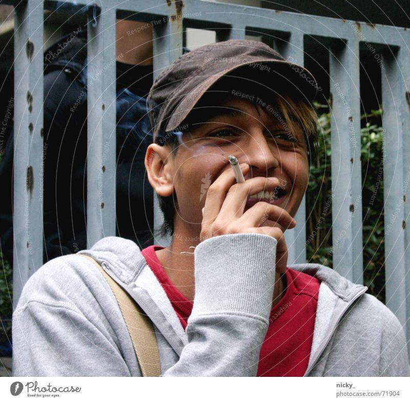 rico rules Mann Freundlichkeit Baseballmütze Zigarette Pause Pullover grau rot braun südländisch Mensch Rauchen lachen Gesicht Geländer kappe Hut