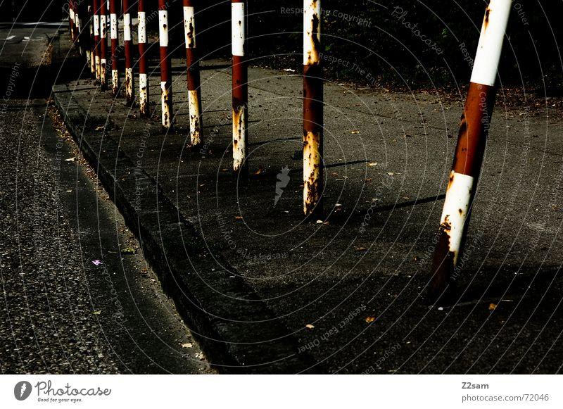 aus der Reihe tanzen rot Straße Schilder & Markierungen Perspektive Bürgersteig Zaun Pfosten Bordsteinkante Fahrbahn
