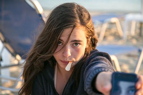 Selbstporträt aufm Handy Lifestyle Ferien & Urlaub & Reisen Tourismus Sommerurlaub Mensch feminin Jugendliche 1 13-18 Jahre Kind Strand brünett sitzen Coolness
