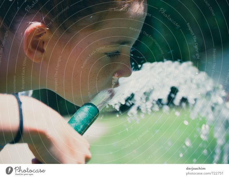 Ein Mädchen hält einen Wasserschlauch in der Hand. Sie trinkt aus dem heraus strömenden Waser daraus. .Quench trinken Wohlgefühl Sommer feminin Mund 1 Mensch