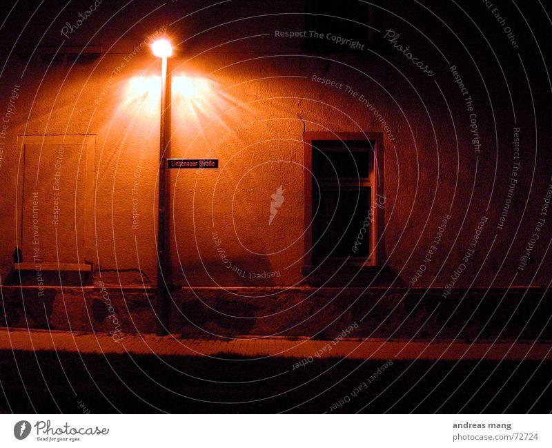 Ein Licht in der Dunkelheit Laterne Straßenbeleuchtung Straßennamenschild Fenster Wand Haus Verfall dunkel unheimlich leer Nacht window alt old verfallen light