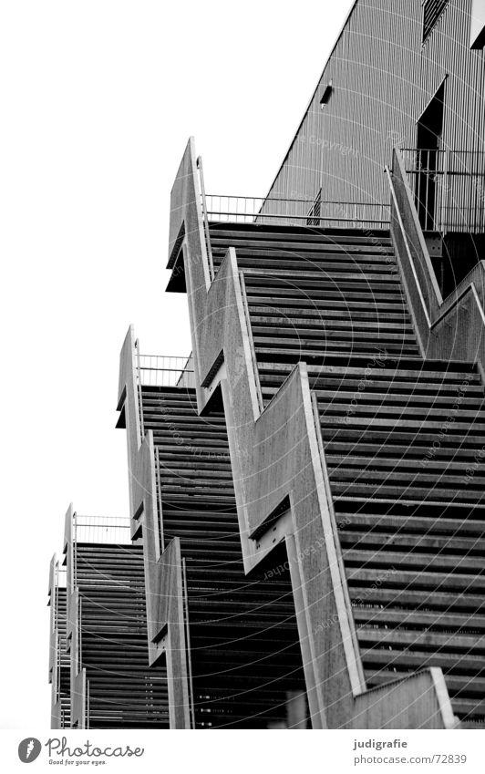 Treppen 4 Gebäude Haus Konstruktion Blick nach unten abwärts Eingang Ausgang schwarz weiß grau trist Geometrie Detailaufnahme Schwarzweißfoto Geländer
