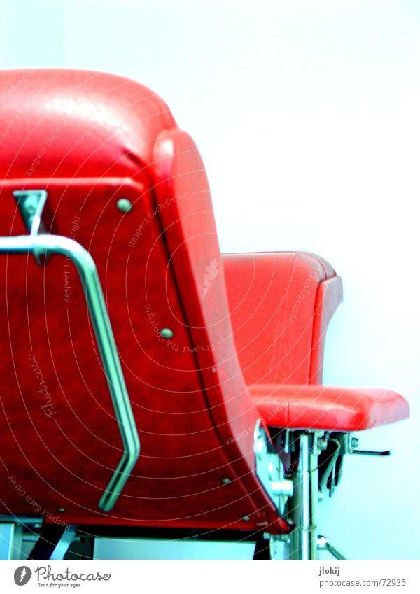 Folterstuhl rot Metall Design Stuhl Stahl Leder Siebziger Jahre Bildausschnitt Anschnitt Objektfotografie Niete Sessellehne Designermöbel Ledersessel Vor hellem Hintergrund Stahlrohrstuhl