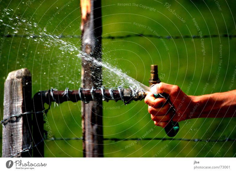 tut gut! Schlauch Brunnen Hand Daumen Finger Stacheldraht Zaun Draht Holz Pfosten nass kalt Kühlung feucht Gras grün Wiese Wasser spritzen Wassertropfen Arme