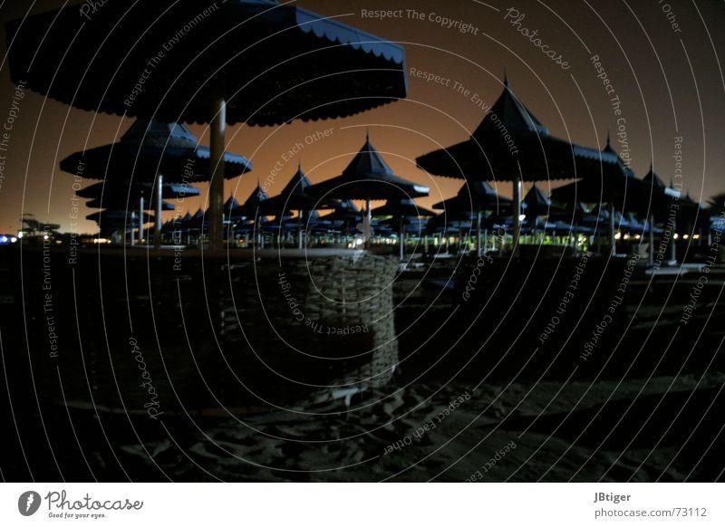 Fang den Hut Sonnenschirm Sonnenuntergang Strand Nacht Geborgenheit ruhig Sand ägypten. urlaub orangefarbener himmel blaue hüte
