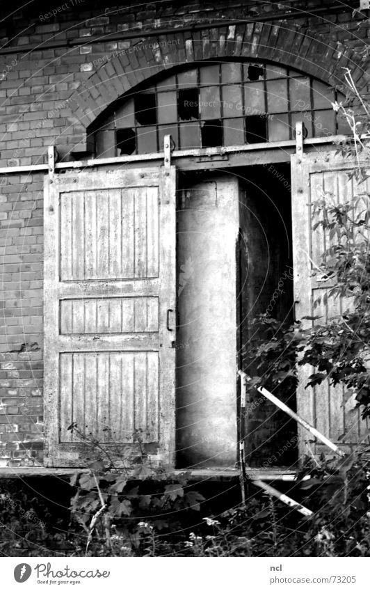 alte Tür s/w Holztür Schiebetür Schiebetor Fenster kaputt gebrochen zerschlagen oben Splitter Bogen Backstein Gießerei Handwerk dreckig vergessen Einsamkeit