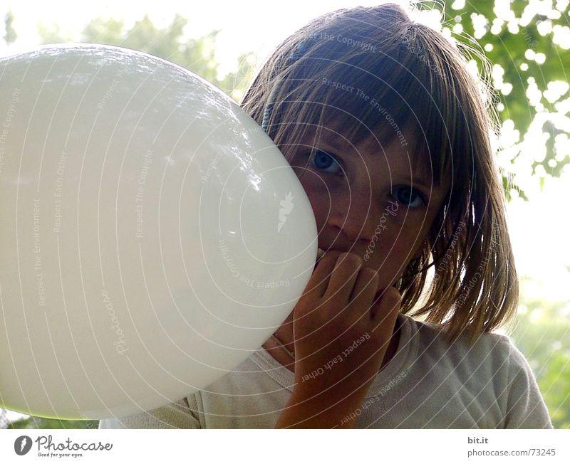 Nachdenkliches, verträumtes, süßes Mädchen mit weissem Luftballon in der Hand im Garten, schaut in die Kamera. Liebes Geburtstagskind draussen in der Natur freut sich über geschenkten Luftballon zu ihrem Fest, hält ihn fest und steckt ihn in den Mund.