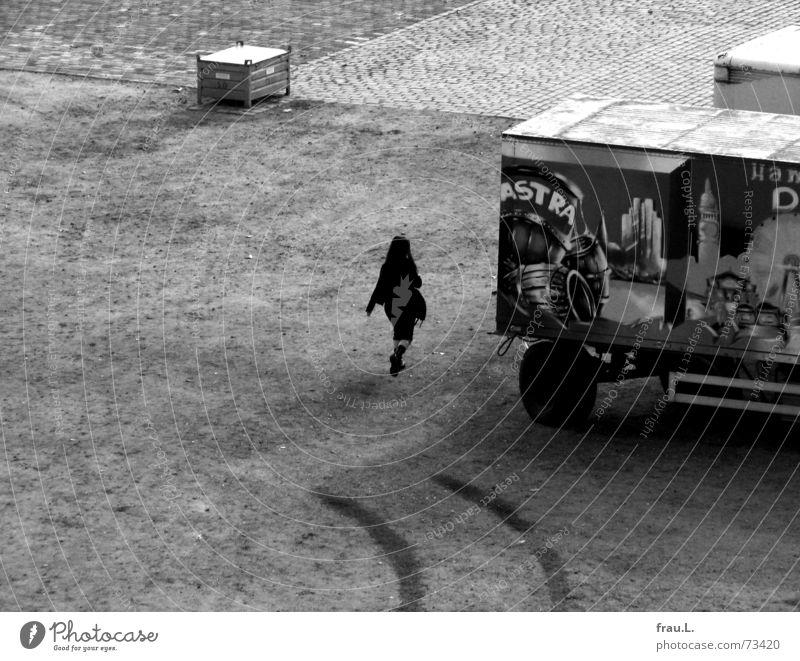 Gundel Gaukeley schwarz Kopfsteinpflaster Platz Frau Stiefel gehen Einsamkeit attraktiv Bauwagen Reifenspuren abgelegen Junge Frau Werbung Mensch Verkehrswege
