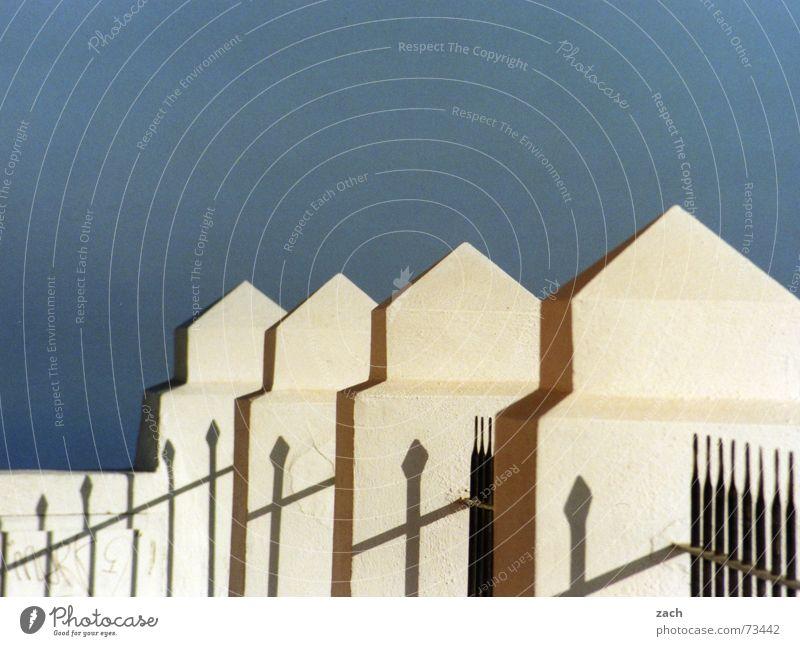 zackig Zaun aufgereiht hintereinander Griechenland diagonal Mauer Grenze Santorin Detailaufnahme Europa obskur Himmel blau Zacken Baumkrone Schatten Reihe