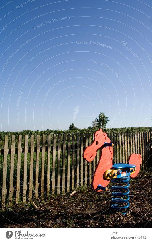 Ritt auf dem Vulkan Himmel blau Einsamkeit Spielen Holz Kindheit Pferd Spielzeug Zaun Holzbrett Schaukel Österreich Spielplatz ungestört Reitsport friedlich